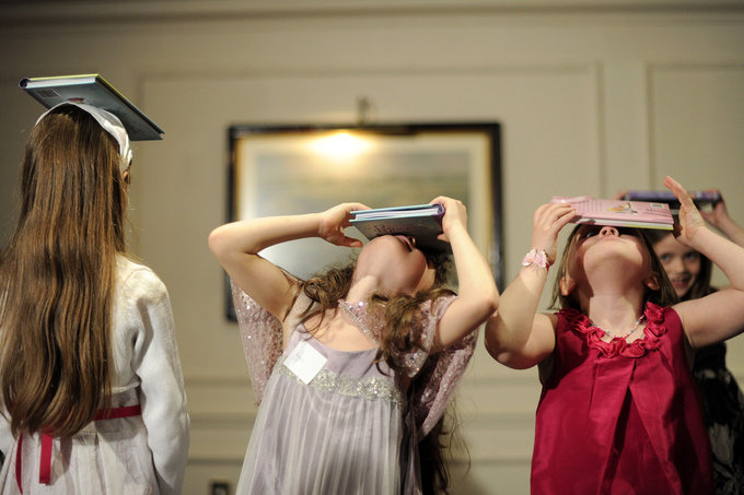 Girls balance books on their heads to practise deportment during the 'Princess Prep' special workshop called 'Regal Rules: An Introduction to Royal Manners & Behaviour' in central London on April 2, 2011. AFP PHOTO / CARL COURT (Photo credit should read CARL COURT/AFP/Getty Images)